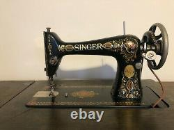 1910 vintage Singer Red Eye sewing machine with oak cabinet. Has belt and works