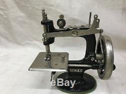 Antique child's singer sewing machine with doll mannequin